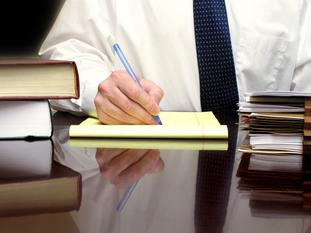 man in white shirt and blue tie writing in legal pad