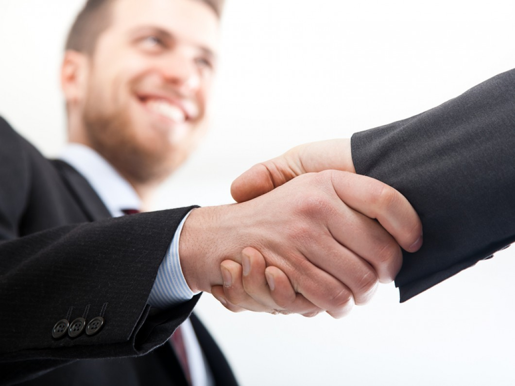 man shaking hands with someone and smiling